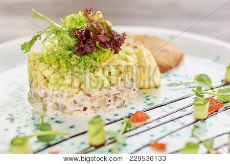 Delicious Salad With Herring. Appetizing Restaurant Dish. Tasty Salad On Plate In Restaurant.