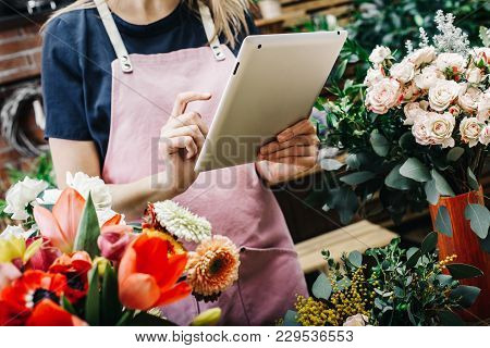 Young Girl Takes Pictures Of Floral Bouquets On A Tablet
