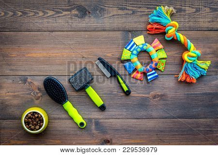 Pet Accessories. Toys Near Bowls With Animal Feed, Grooming Equipment On Dark Wooden Background Top