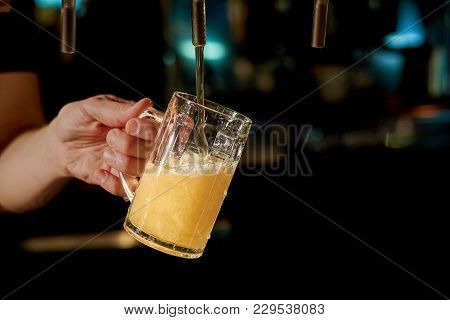Close Up Bartender Hand Pouring Beverage. Barman Hand At Beer Tap Pouring Draught Lager Beer In Glas