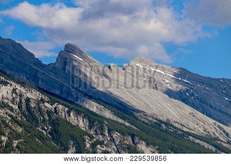 Rocky Mountains With Clouds Floating Above In Alberta Canada