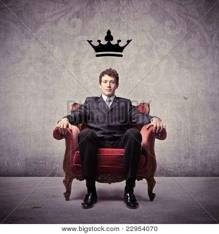Businessman sitting on an armchair with a crown over his head