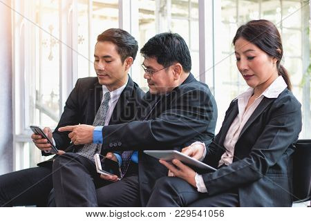 Bussiness People Looking And Smiling Content At Cell Phone