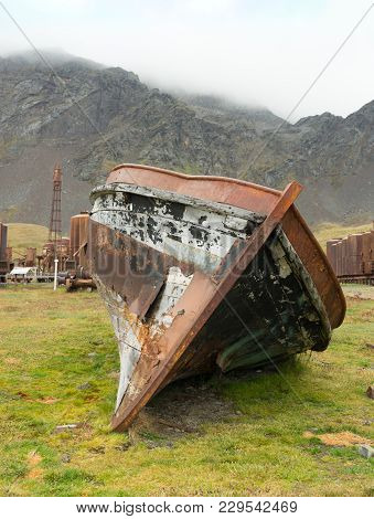 A Damaged Boat With Rusted Sheet Metal Coming Off Exposing The Wood Beneath. A Rusted Tower, Rusty T
