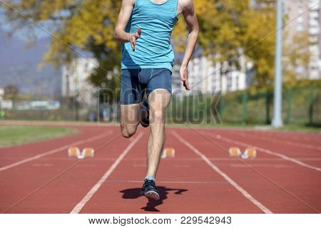 Man Runner In Blue Shirt And Shorts And Sport Shoes In Steady Position Before Run At Start Of Race