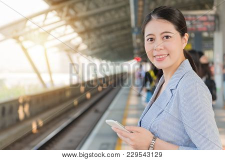 Girl Holding A Mobile Phone Standing On Platform