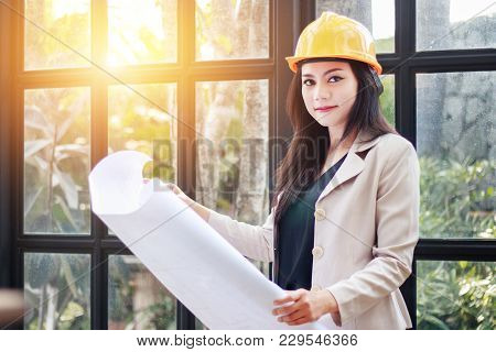 Portrait Of Beautiful Asian Woman Architect Builder With Yellow Helmet Hard Hat Studying Blueprint P