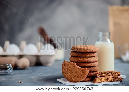 Oatmeal Cookies In A Neat Stack With A Milk Bottle And Baking Ingredients Out Of Focus. Baking Conce