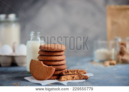 Stack Of Sugar Buckwheat Cookies On A Stone Background With Baking Ingredients Out Of Focus. Cooking