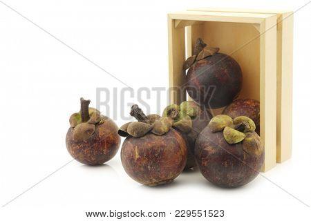 mangosteen fruits (Garcinia mangostana linn) in a wooden box on a white background