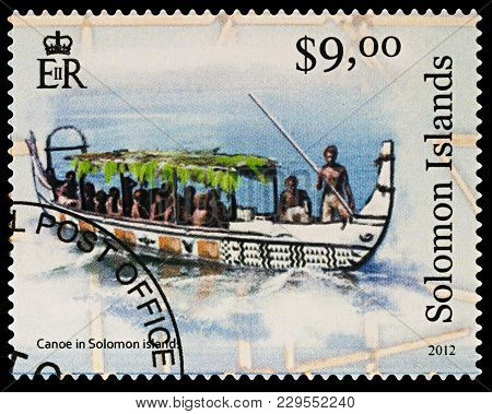 Moscow, Russia - March 04, 2018: A Stamp Printed In Solomon Islands Shows Big Canoe With Passengers