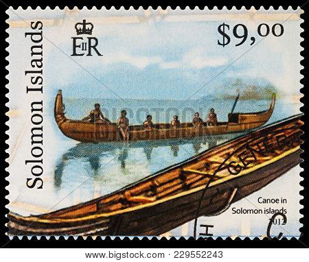Moscow, Russia - March 04, 2018: A Stamp Printed In Solomon Islands Shows Canoe With People In Solom