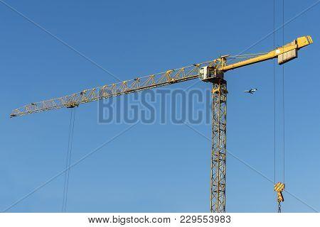 High-altitude Crane Lifts Cargo, Against The Blue Sky.