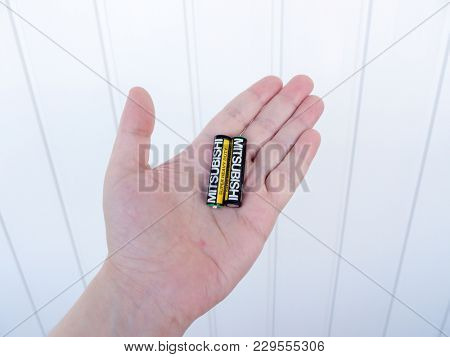 GOMEL, BELARUS - FEBRUARY 8, 2018: Mitsubishi AA alkaline battery on a hand background. The Mitsubishi Group is a group of autonomous Japanese multinational companies.