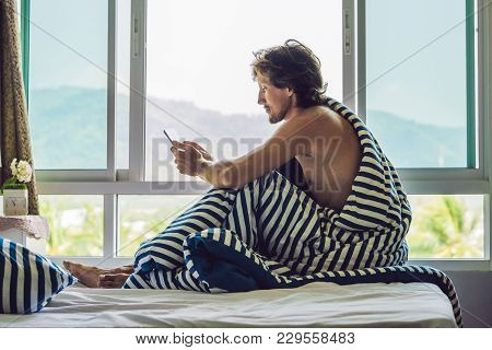 The Man Woke Up In The Morning And Reads The News On The Tablet In The Background Of A Window With A