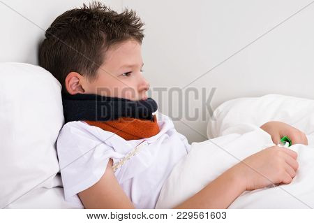 Boy Sick In Bed Neck Rewound With Scarf