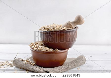 Oat Flakes  In Ceramic Bowl And Wooden Spoon On White Vintage Wooden Background, Selective Focus Cop