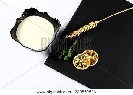 Yoghurt Plate, Mint Leaves, Slices Of Lemon, Wheat, On A Black Shale Board, On A White Background To