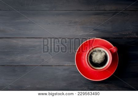 Coffee With Foam In Red Cup With Saucer On Dark Wooden Table. Copy Space. Top View