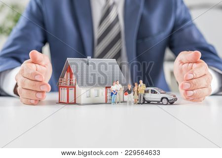 Insurance House, Car And Family Health Live Concept. The Insurance Agent Presents The Toys That Symb