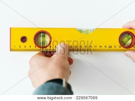 Man using water level meter measuring the wall