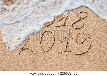 New Year 2019 Is Coming Concept - Inscription 2018 And 2019 On A Beach Sand, The Wave Is Almost Cove