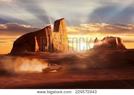 Car In Motion In The Dasht-e Lut Desert Against Sunset. Beautiful Rays Under The Rocks. Iran. Kerman