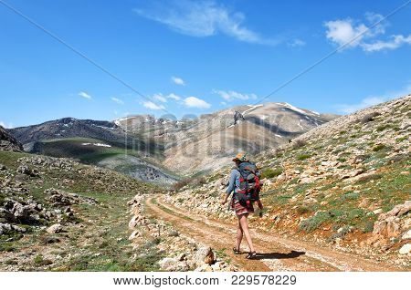 Backpacker With Backpack Walking On A Dirt Road In Mountains, Southern Turkey