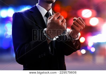 Businessman In Handcuffs On The Streets At Night