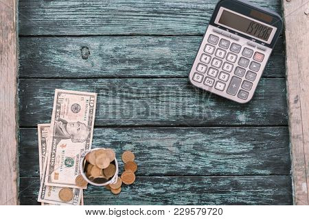 Calculator With Money And Pennies On A Wooden Green Background. Business Concept.