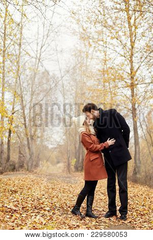 Loving Couple Walks In The Autumn Park, Hugs And Kisses. Woman In The Arms Of A Man In The Woods In