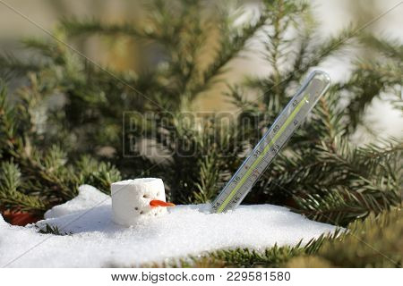 Old Thermometer And Melted Snowman On A Spring Sunny Day / Climatic Changes In Global Warming