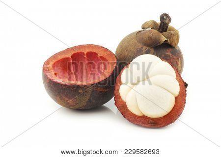 mangosteen fruit (Garcinia mangostana linn)  and a cut one on a white background