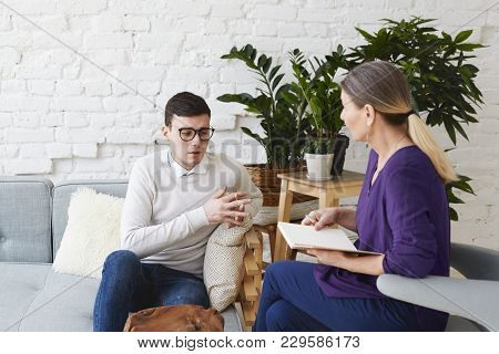 Candid Shot Of Young Man In Glasses Talking About His Problems During Psychological Therapy Session,