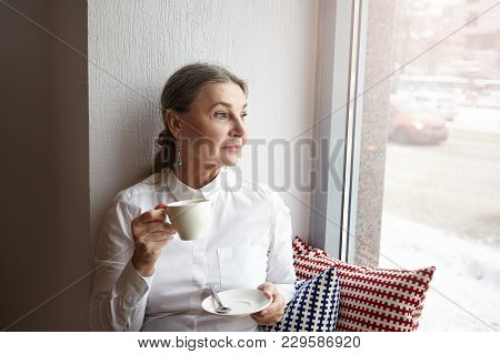 Beautiful Middle Aged Female With Gray Hair And Blue Eyes Sitting At Cafeteria On Windowsill, Enjoyi