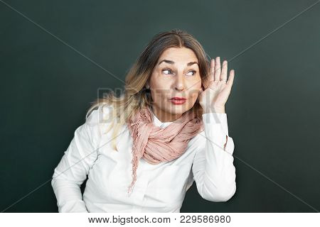 Nosy Funny Senior 60 Year Old Woman Holding Hand To Ear, Trying To Listen To Juicy Gossip Or Secret