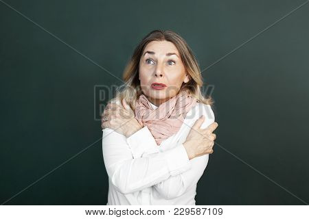 Studio Shot Of Shivering Or Trembling Middle Aged Attractive Woman Hugging Herself To Warm While Fee