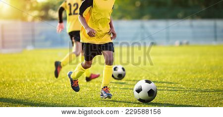 Football Training On The Pitch. Boys On Soccer Training Session. Kids Footballers Running The Ball.