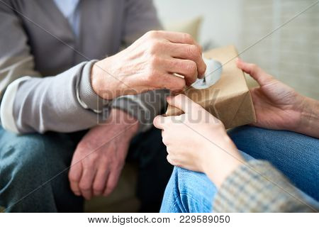 Close Up Of Senior Man Taking Tissue Out Of Box To Wipe Tears During Therapy Session