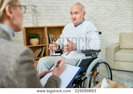 Portrait Of Disabled Senior Man In Wheelchair Sharing Problems With Psychiatrist During Therapy Sess