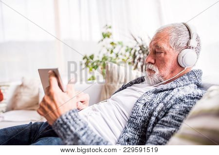 Senior Man With Tablet And Headpones Relaxing At Home. Old Man Listening To Music.