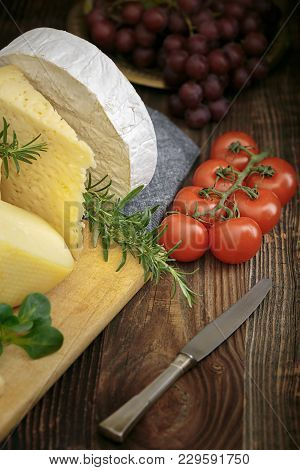 Cheeses With Basil, Rosemary, Tomatoes And Grapes.