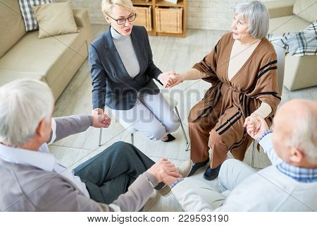 High Angle View At Senior People Holding Hands In Group Therapy Session Lead By Female Psychiatrist,