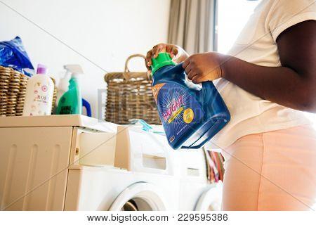 Young teen girl washing clothes using washing machine