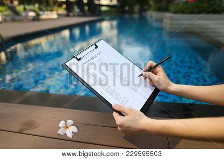 Female Hand Holds Out Pen, Fills Out Visa Application Form In United States. Sunny Portrait On Pool
