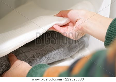 Close Up Women Hand Taking A Towel From A Stack Of Towel On Shelf In Bathroom