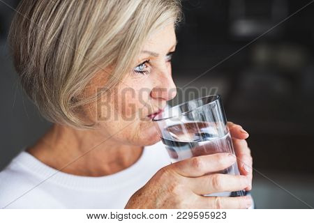 Senior Woman In The Kitchen. An Old Woman Inside The House, Drinking Water. Close Up.