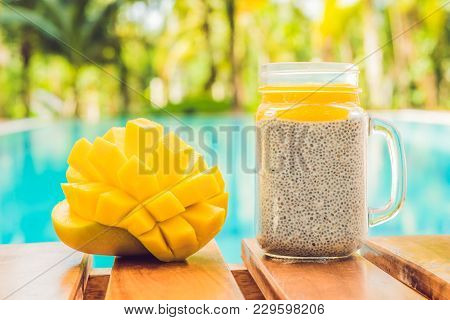 Chia Seed Pudding With Almond Milk And Fresh Mango Topping On The Background Of The Pool.