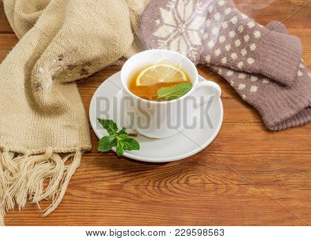 Tea With Lemon And Mint Against Of Woolen Mittens, Scarf