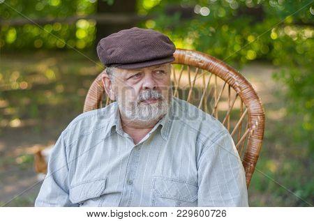 Outdoor Portrait Of Caucasian Senior Man Sitting In A Chair In Summer Park